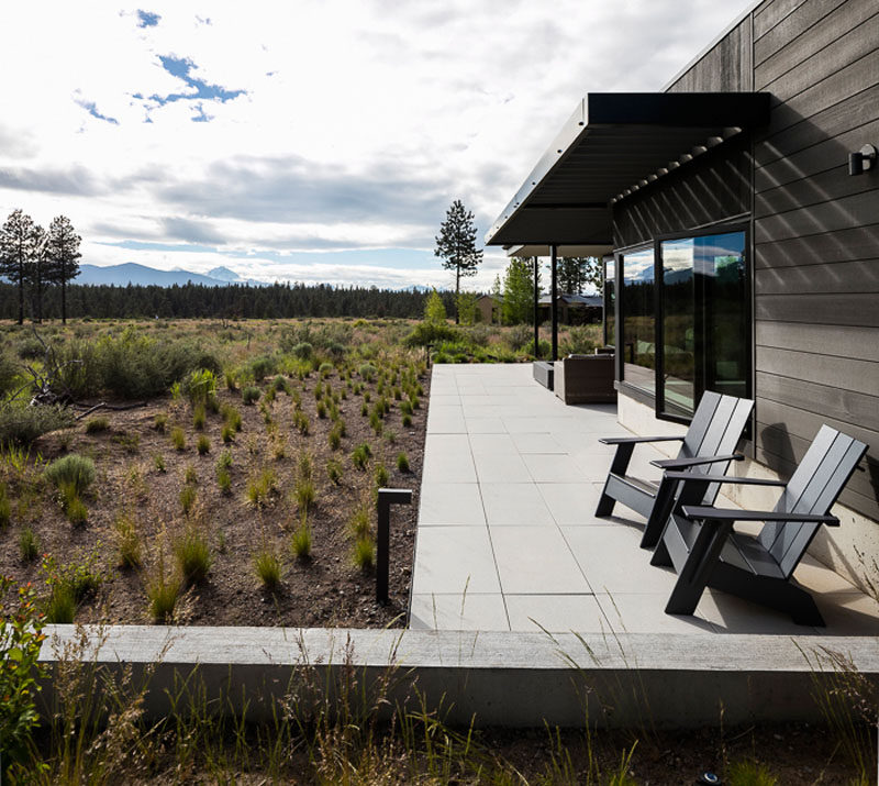The modern patio of this house features a large format precast concrete pavers. #Patio #Landscaping #LandscapeDesign #HouseDesign