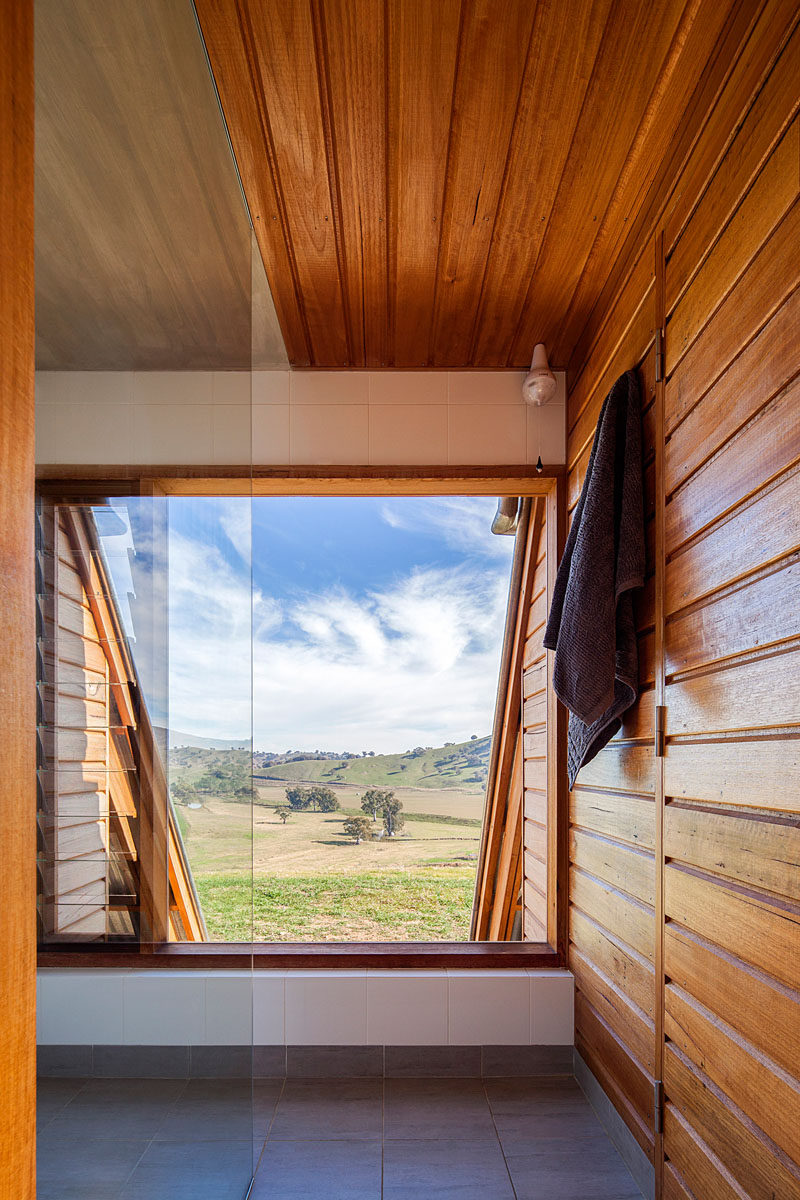 This large window in a bathroom provides views of the surrounding farmland. #Windows #Bathroom #WoodWalls