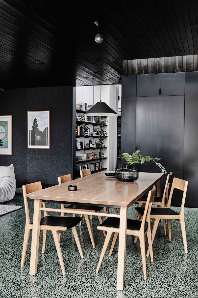 This modern house extension features a dining area furnished with a light wood table and chairs. Off to the side of the dining room is a shelving unit for the home owners book collection. #DiningRoom #Shelving #ModernDiningRoom #BlackWalls