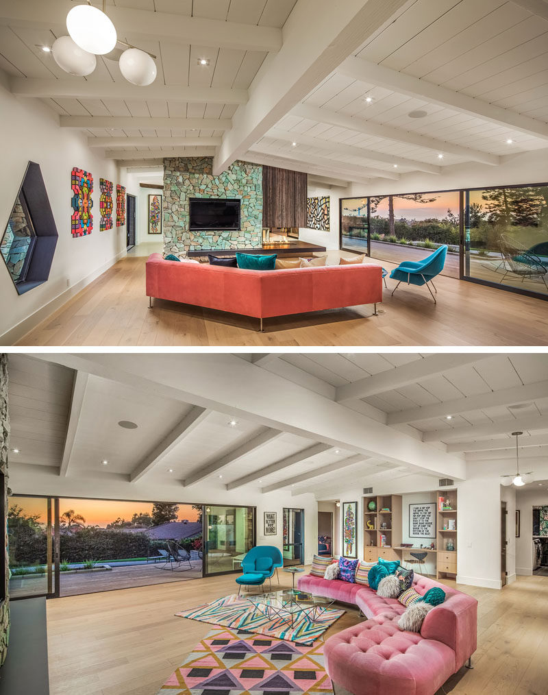 Stepping inside this renovated mid-century modern house, the living room is large and open, withsteel and glass partition walls and windows that open it to the deck. #LivingRoom #StoneFireplace #TurquoiseStone #ModernInterior