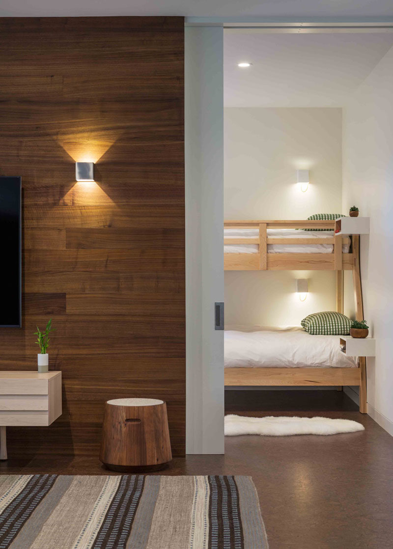 This modern house has a guest room with bunk beds that are located off a casual living room. #BunkBeds #PocketDoor #WoodAccentWall