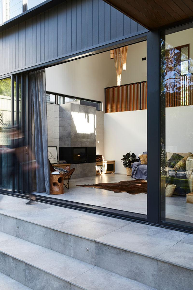 This modern living room, which is open to the backyard, has astone fireplace and an abundance of natural light. #Fireplace #StoneFireplace #LivingRoom