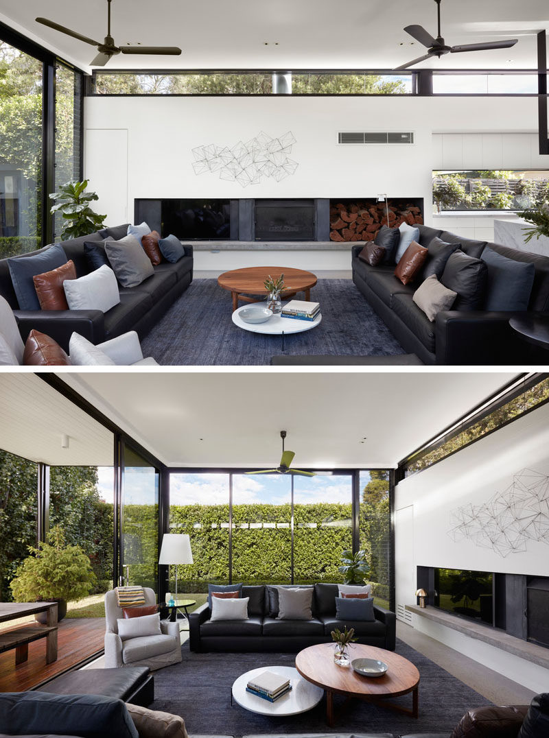 This modern living room has a fireplace andfull height windows that provide views of the lush trees and greenery. #LivingRoom #ModernLivingRoom #Fireplace #Windows