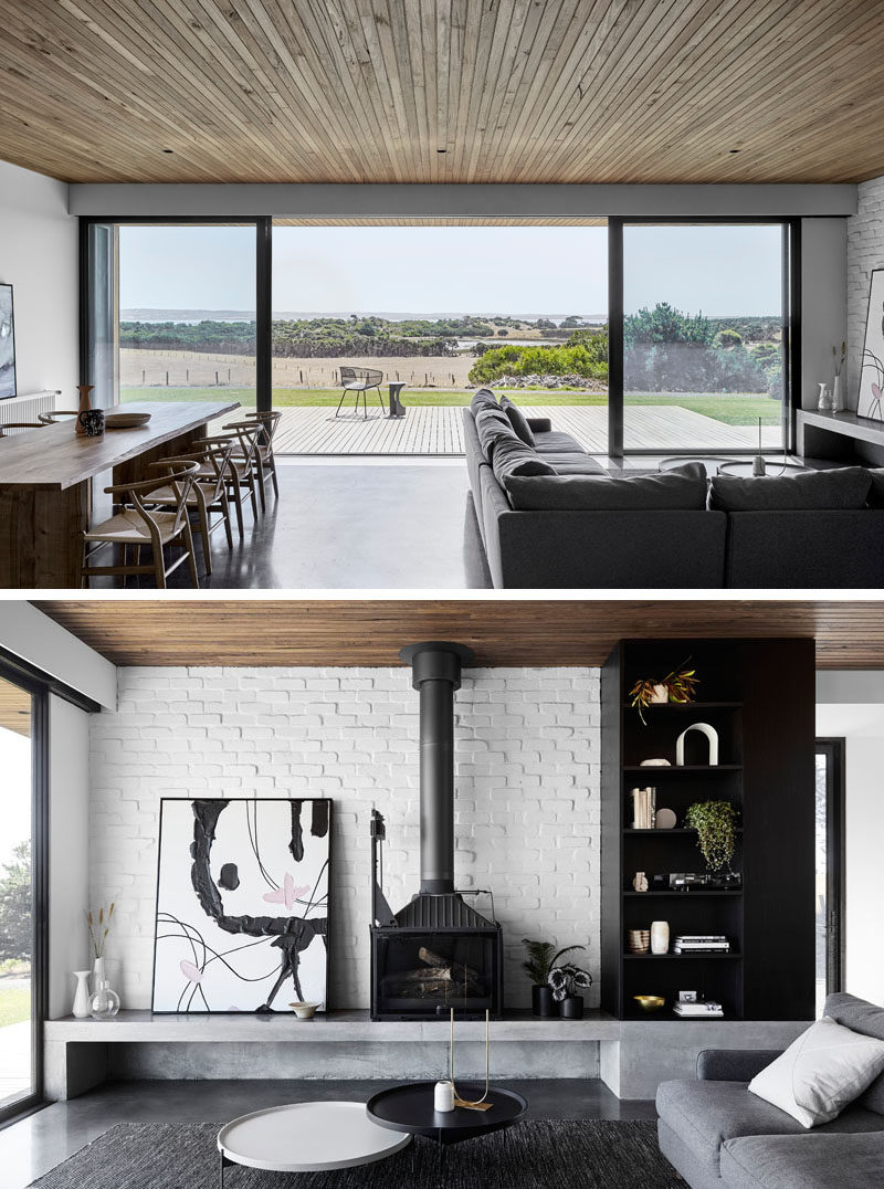 The dining and living areas of this modern house open up to a wood deck that has sweeping views of the coastline and water beyond. #ModernInteriorDesign #WhiteBrick #BlackFireplace #Deck #SlidingGlassDoors #WoodCeiling