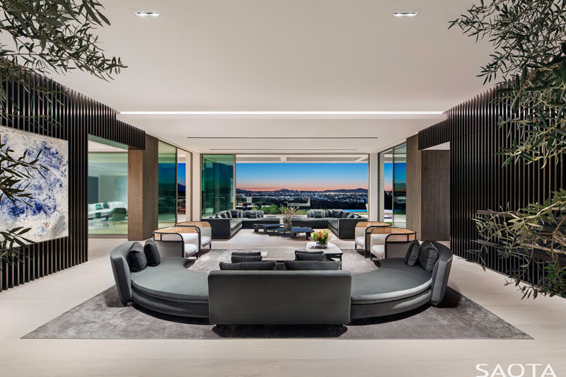 In this great room, there are two separate sitting areas that have been positioned to take advantage of the perfectly framed view. #CurvedCouch #GreatRoom #ModernLivingRoom