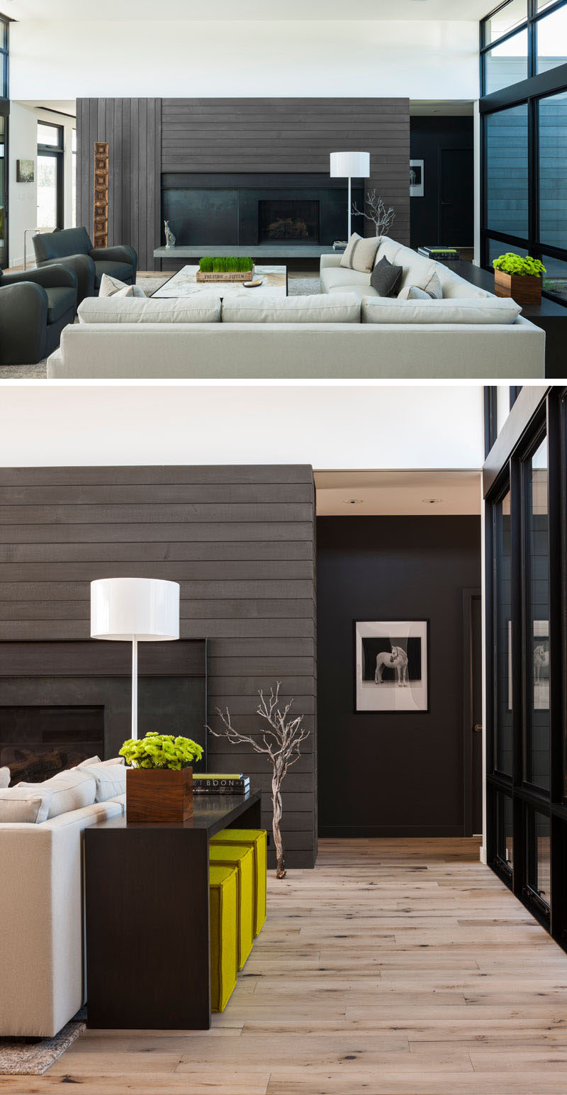 This modern living room features a stained cedar wood accent wall surrounds a black fireplace, while a light colored couch, high ceilings and plenty of windows help to keep the interior bright. #StainedCedar #LivingRoom #InteriorDesign