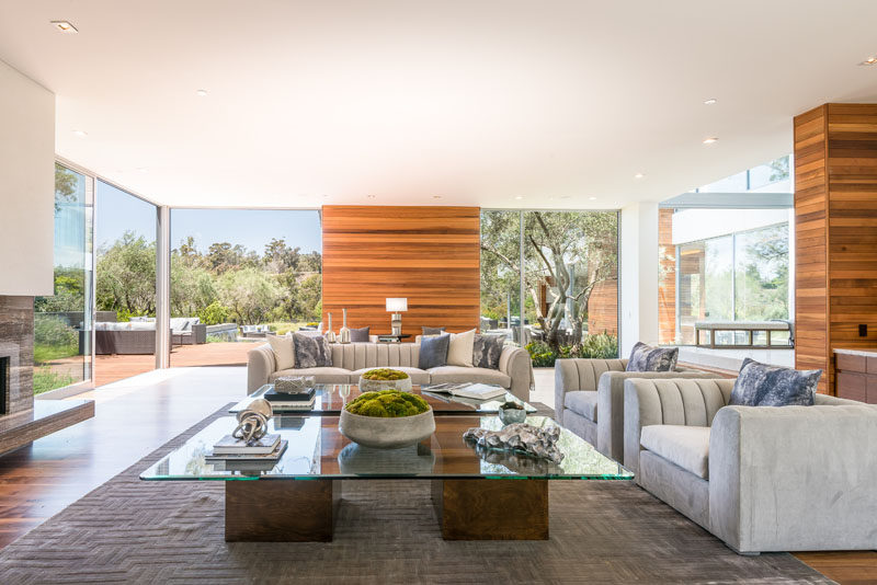 This modern house has a formal living room with a fireplace and floor-to-ceiling windows and glass doors that provide access to a terrace outside. #LivingRoom #InteriorDesign #ModernLivingRoom