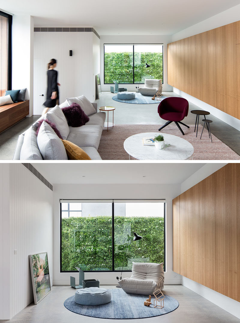 This modern living room features a small quiet reading area that has large windows to fill the area with natural light. #LivingRoom #ModernLivingRoom #Windows