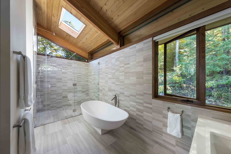 In this modern master bathroom, light colored tile and plenty of windows keep the space bright, while a glass enclosed shower is located at the end of the bathroom, with a freestanding bathtub nearby. #MasterBathroom #ModernBathroom #Windows #Skylight