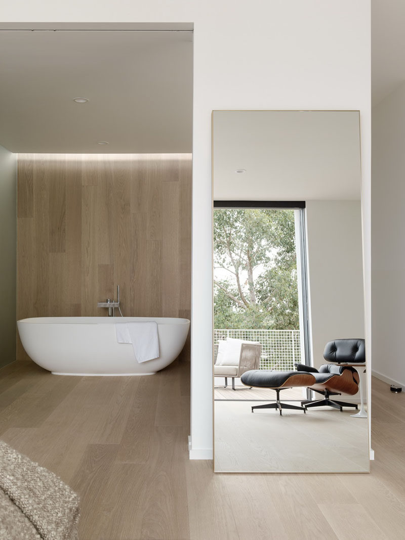 In this modern master bathroom, the wood flooring in the bedroom travels up the wall and becomes the backdrop for a freestanding bathtub. #WoodAccent #MasterBathroom #WoodFloors