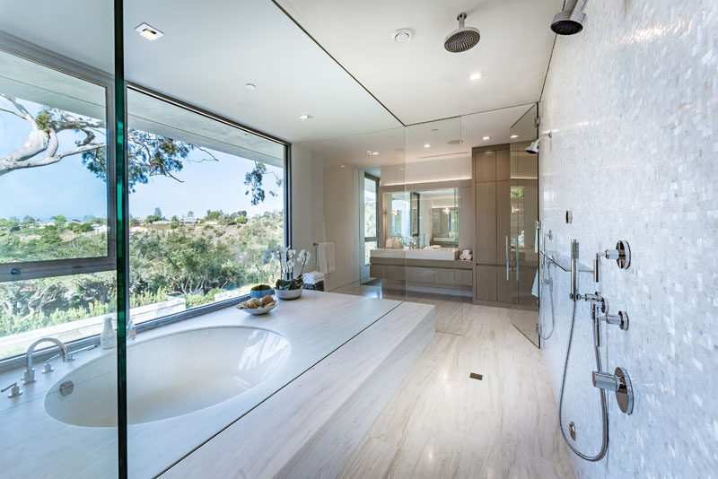 In this modern master bathroom, there's a built-in bathtub positioned in front of the windows, while a rainfall shower is positioned next to it. #MasterBathroom #EnsuiteBathroom #BuiltInBathtub