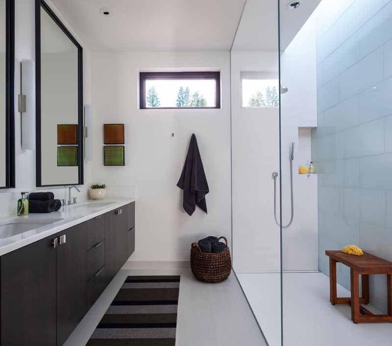 In this modern master bathroom, a skylight helps to keep the glass enclosed shower bright, while a dark vanity ties in with the rest of the dark wood used throughout the home. #MasterBathroom #ModernBathroom