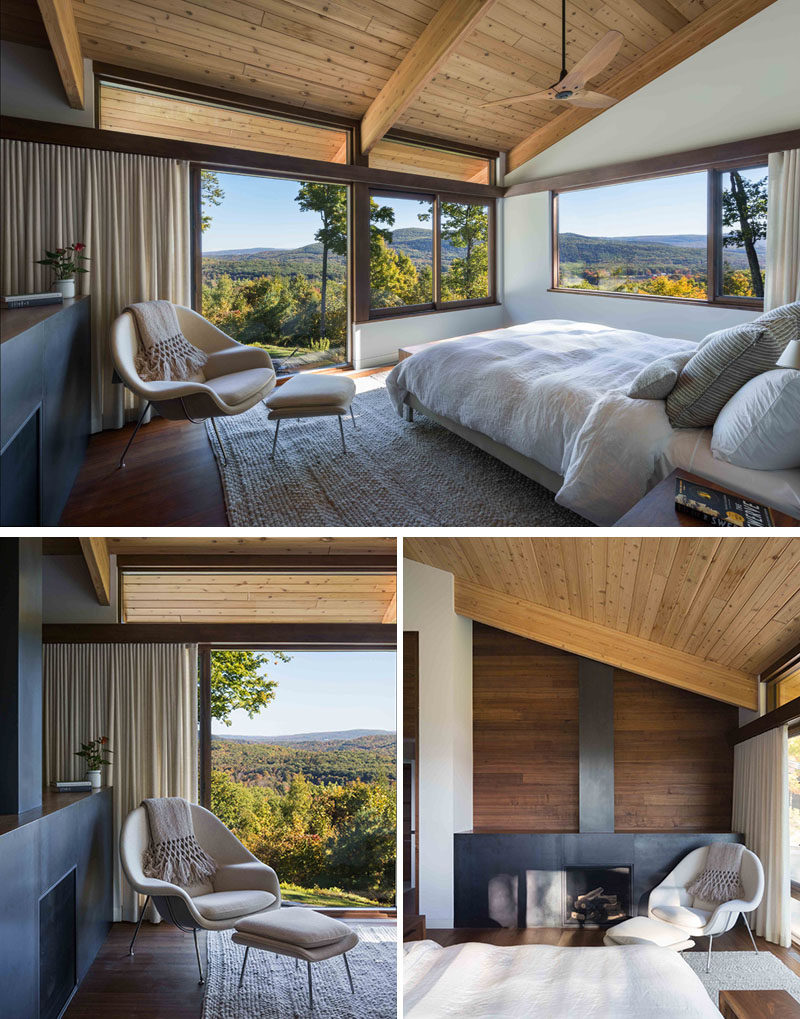 This modern master bedroom has large windows, a sloped wood ceiling and a fireplace. #MasterBedroom #Fireplace #Windows #WoodCeiling