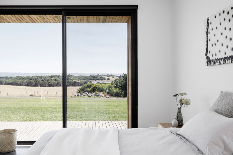 In this modern bedroom, the furnishings have been kept simple yet comfortable, and a sliding glass door opens to the deck. #ModernBedroom #BedroomDesign