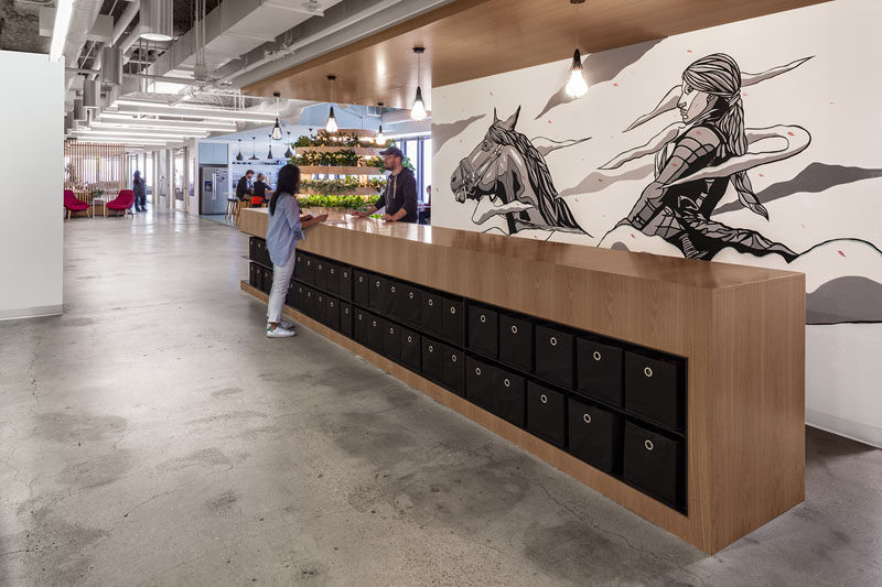 In this modern healthcare office , the company's icon, Joan of Arc, has been added as a large contemporary mural that spans the width of a wall. #Mural #Art #OfficeDesign #Workplace #InteriorDesign