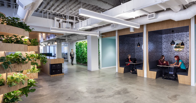 This modern office has open booths for small meetings, and nearby is a green wall and a Growroom that adds touches of nature to the environment. #Booths #Workplace #OfficeDesign #Greenwall