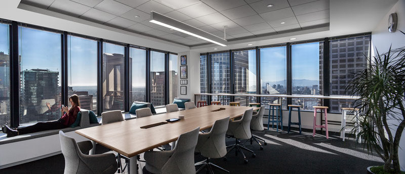 In this large meeting room, additional seating has been added in the form of window seats with backrests and a counter with stools. #OfficeDesign #ModernBoardroom #WindowSeats