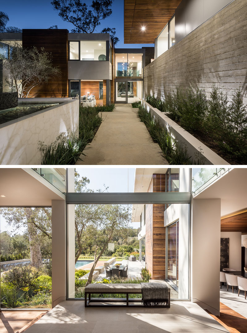 At the front of this modern house, a path that's positioned between aboard-form concrete wall, and a cascading garden and fountain, leads to the front door and through to the foyer with views of the backyard. #Foyer #Landscaping #Concrete #Entryway