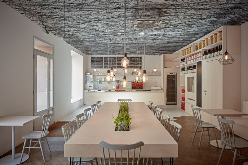mars.s architects have designed a modern bistro with an irregular web semi-transparent suspended ceiling made from black string. #ModernBistro #ModernInterior #ModernRestaurant #InteriorDesign #Ceiling