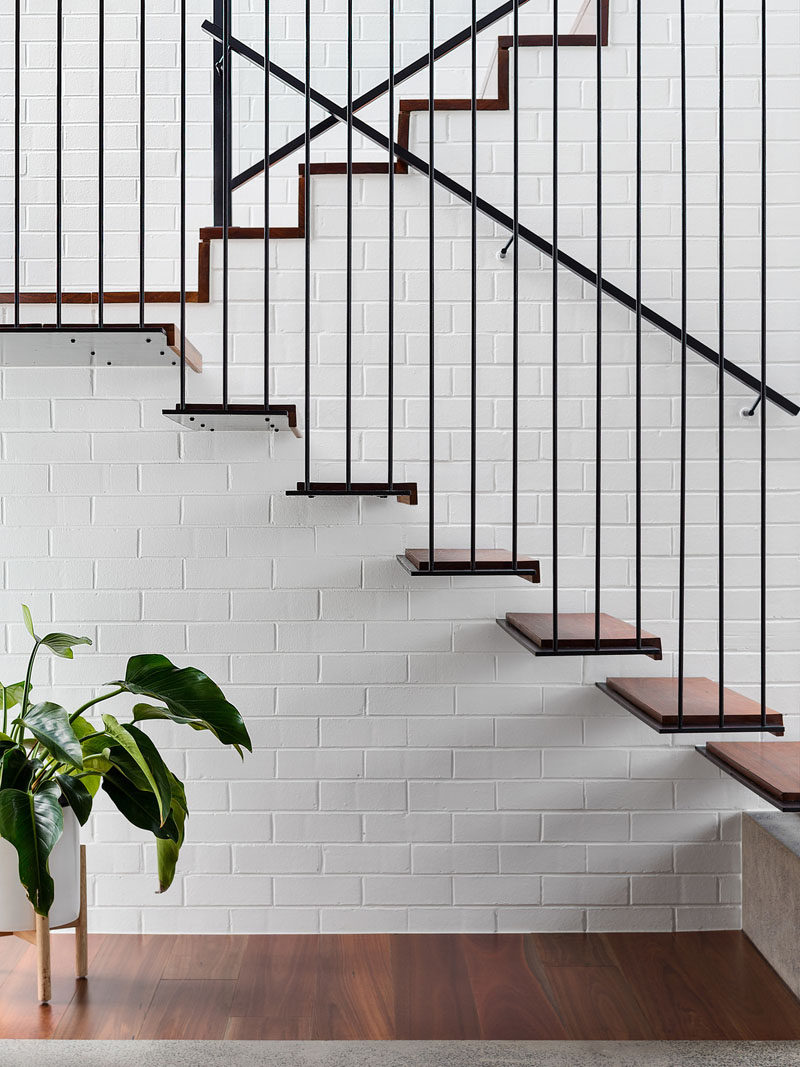 These stairs, which are minimalist in their design, transition from being open to being part of the white painted brick wall. #ModernStairs #MinimalistStairs #WhiteBrick