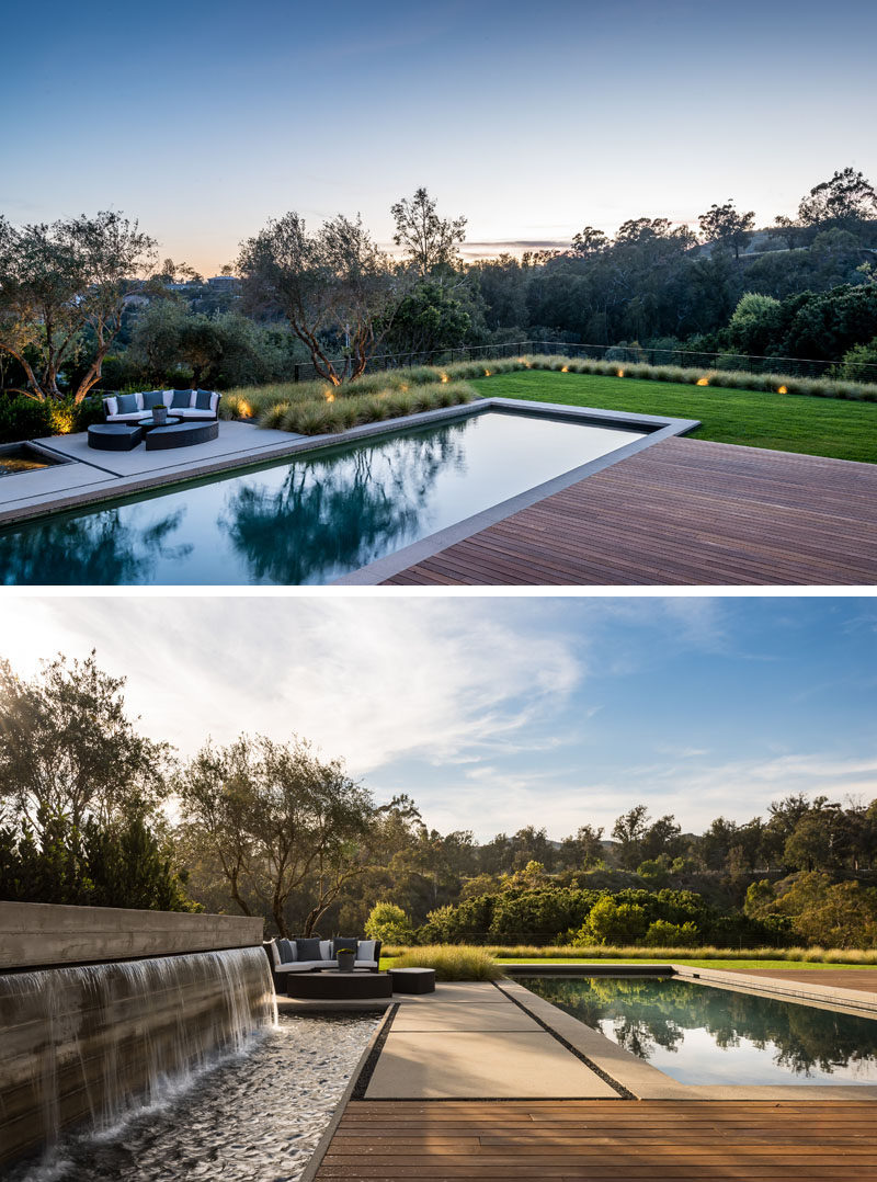 This modern backyard has a water feature, a 50-foot pool with a spa, and a wooden deck. #ModernBackyard #SwimmingPool #WaterFeature #Landscaping