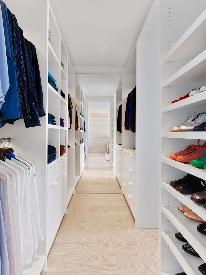 This modern walk-in closet as wide-plank Douglas Fir flooring and plenty of floor-to-ceiling shelving space. #WalkInCloset #InteriorDesign #Closet