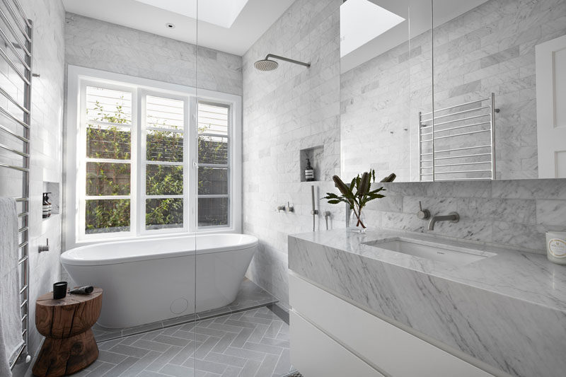 In this modern bathroom, floor-to-ceiling grey tiles have been installed and a freestanding bathtub was added in front of the windows. #ModernBathroom #GreyBathroom #FreestandingBathtub