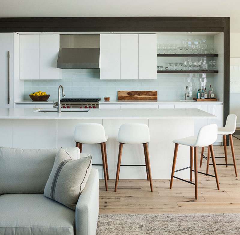This modern kitchen has a white lacquer finish, with a glossy tropical white glass tile backsplash. The design of the kitchen island includes an overhang to allow for seating. #ModernWhiteKitchen #KitchenDesign #InteriorDesign