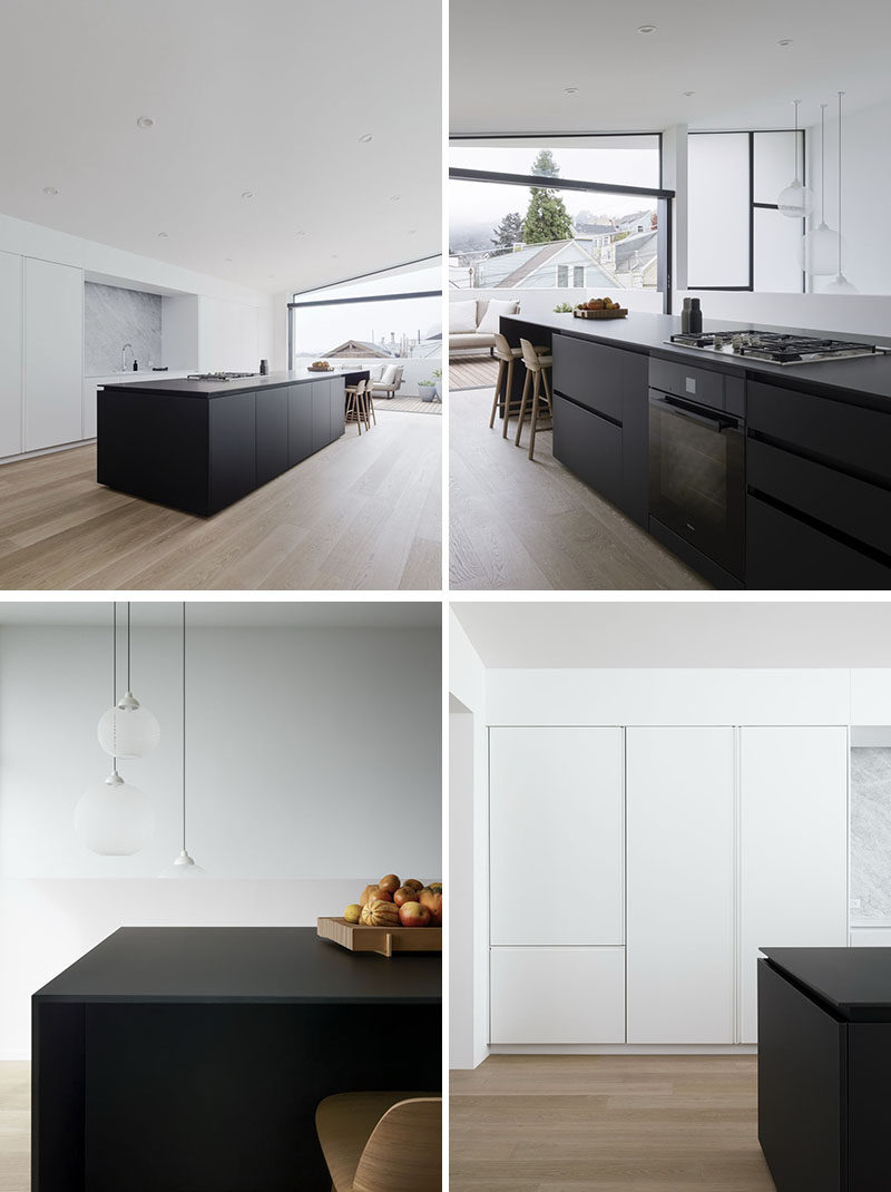 This kitchen is minimalist is in its design, with a striking and bold black kitchen island with an extended section for casual dining. The kitchen opens up to an outdoor space that overlooks the street. #MinimalistKitchen #BlackKitchenIsland #WhiteCabinets