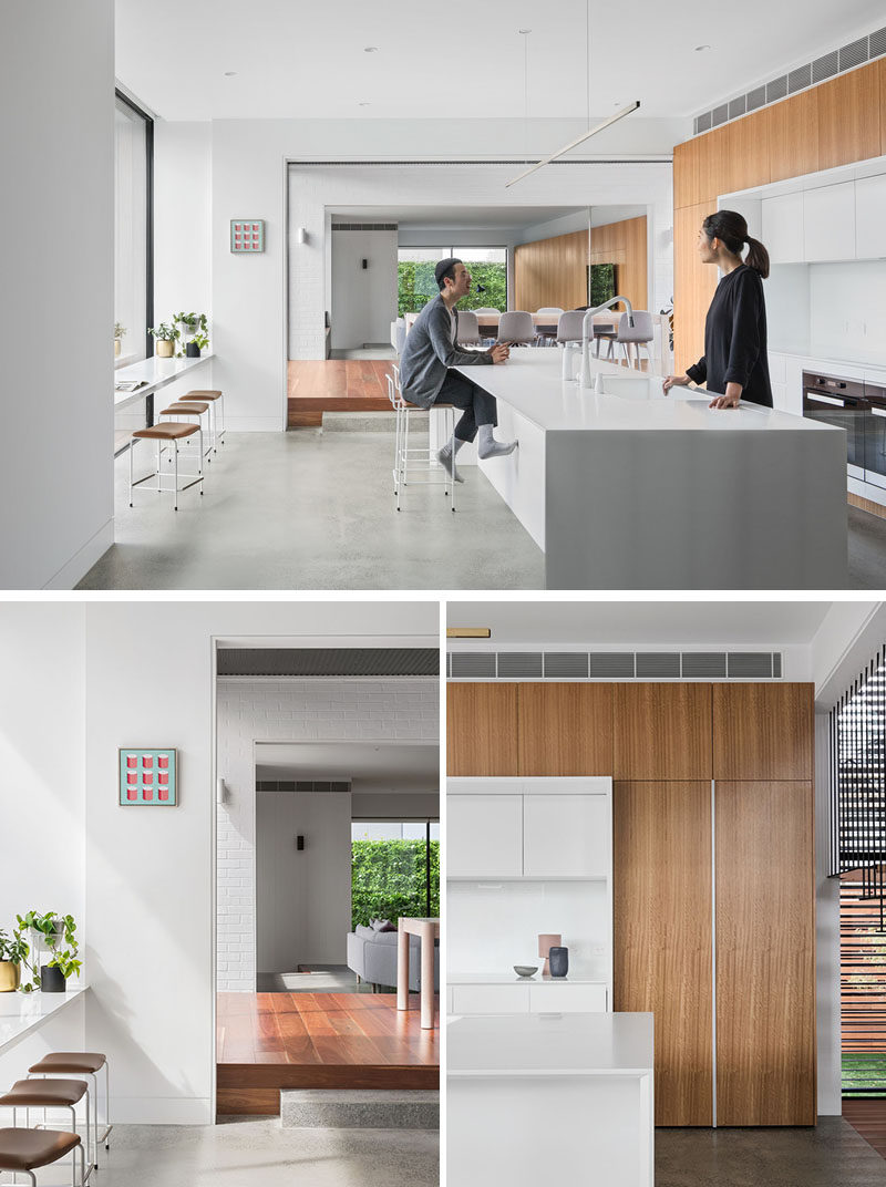 In this modern kitchen, a large white island creates plenty of counter space, while facing the window is a counter with stools, that allows people to relax and look outside. The kitchen also features integrated joinery with a concealed fridge. #ModernKitchen #WhiteKitchen #LargeKitchenIsland