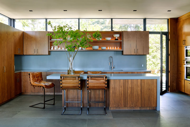 This modern kitchen has soft blue countertops and backsplash, with wood cabinetry and open shelving with lighting. #BlueCountertops #WoodCabinets #KitchenDesign #ContemporaryKitchen