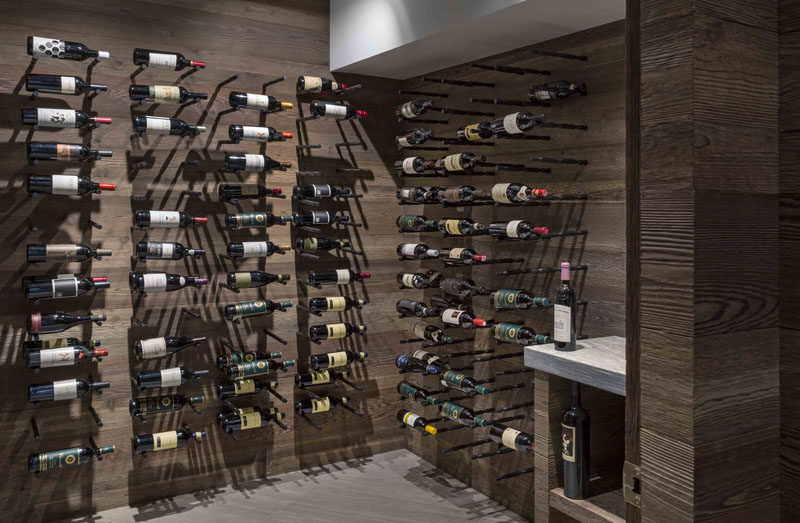 This modern wine cellar has wood lined walls and storage space for displaying the wine collection. #WineCellar #WineStorage