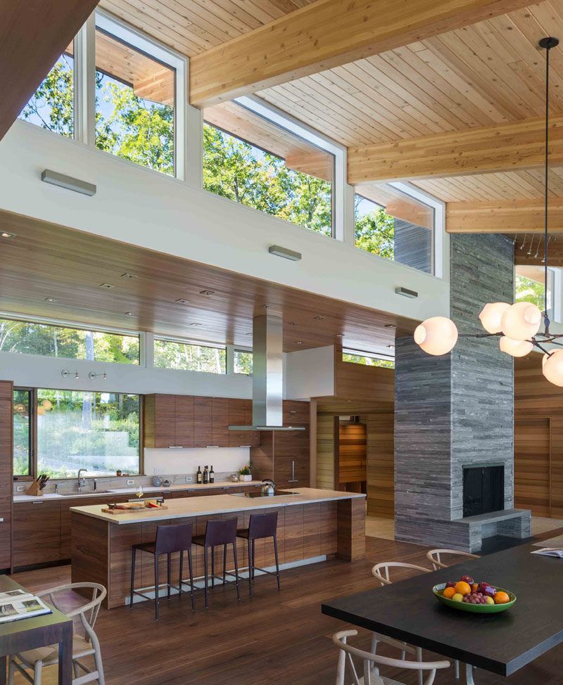 This modern kitchen has dark wood cabinets with white countertops, while a large island provides an additional place for seating. #ModernKitchen #WoodKitchen #KitchenDesign