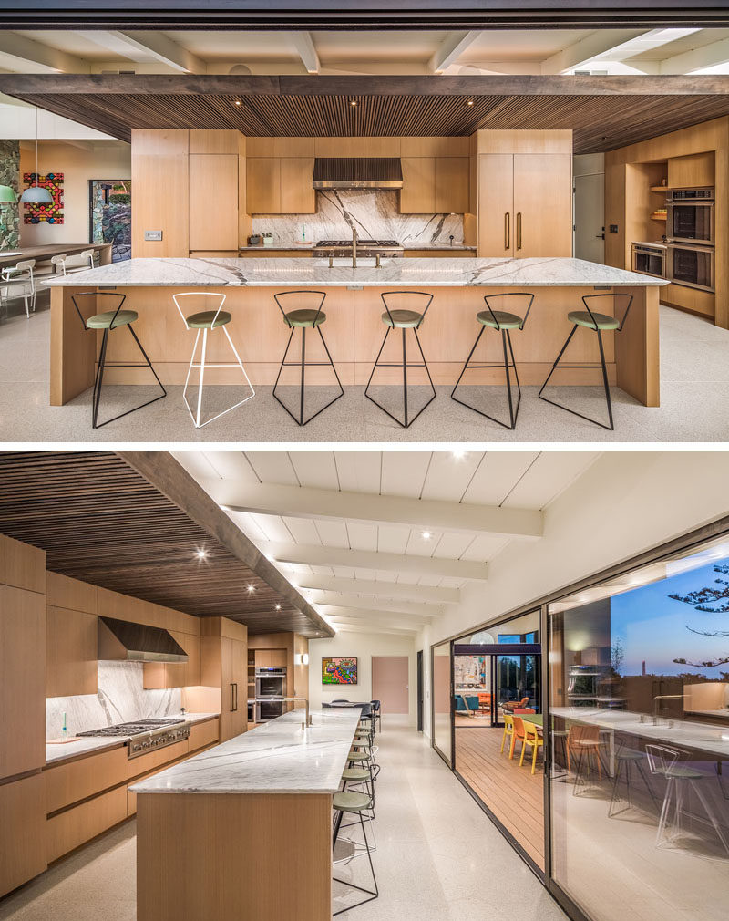In this modern kitchen, there's a wood slat ceiling, and pantry doors sit flush within a full height hallway of wood cladding. A large island, with space for six people to sit at, ensures there's always plenty of seating when entertaining.