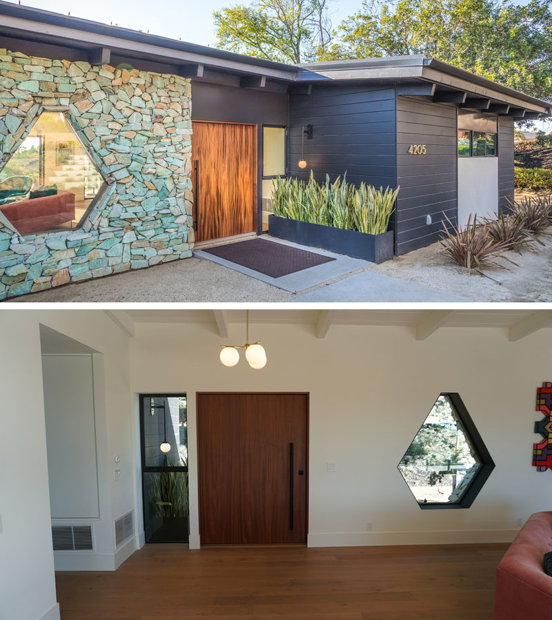 At the front of this renovated mid-century modern house is an oversized mahogany pivoting front door and a one-of-a-kind steel framed custom hexagon window. #PivotingFrontDoor #OversizedDoor #StoneWall #CustomWindow #Window