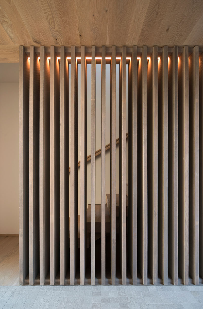 A wood slat partition with hidden lighting wraps around the stairs that lead to the upper floor of this home. #WoodPartition #WoodSlats #WoodSlatPartition