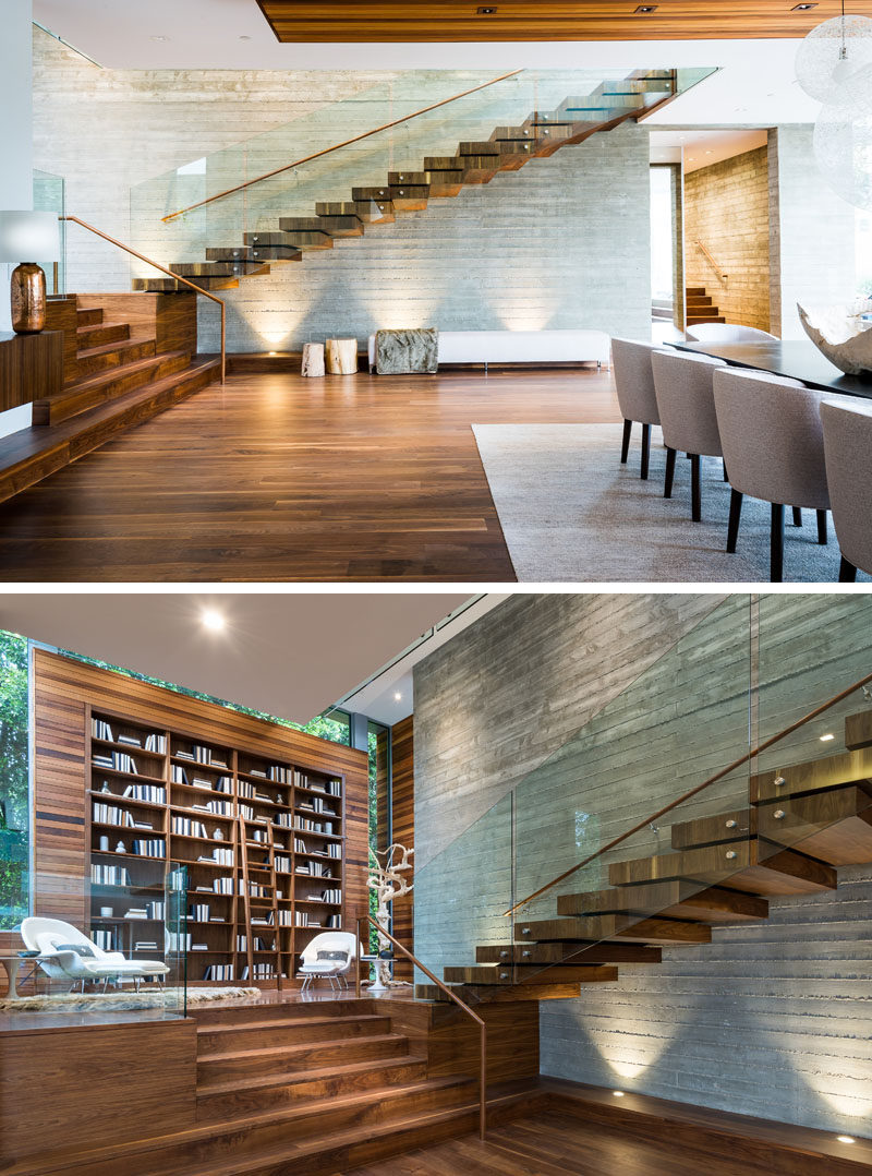 This modern wood and glass floating staircase has an enlarged landing that serves as a formal library with a 15-foot high built-in bookcase. #Library #HomeLibrary #Staircase #FloatingStairs #InteriorDesign #Bookcase