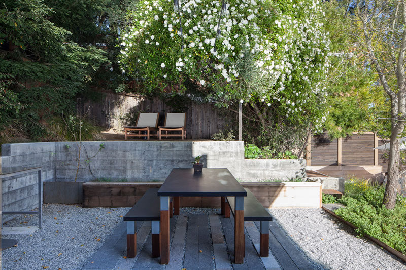 This modern backyard has several areas for relaxation, like the raised outdoor lounge area within the trees, and an outdoor dining patio. #ModernLandscaping #OutdoorDining #Garden #Backyard #LandscapeDesign