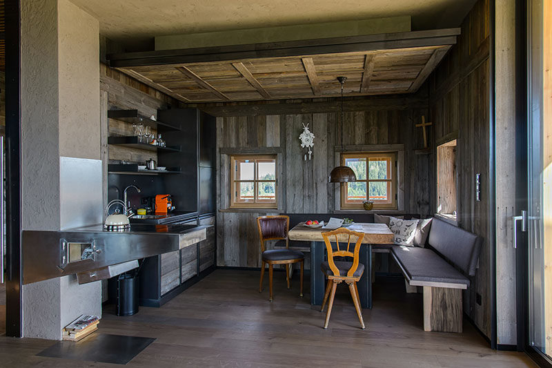 This rustic modern mountain chalet has a small kitchen with a fire place, and a corner dining area with banquette seating. #RusticModern #SmallKitchen #MountainChalet #BanquetteDining