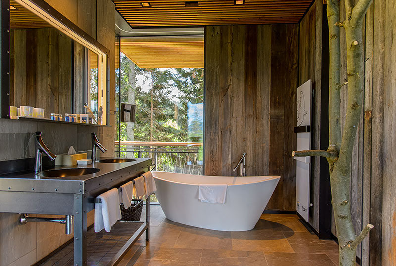 In this rustic modern bathroom, the freestanding bathtub is positioned to look out towards the trees through the floor-to-ceiling corner windows. #RusticModern #Bathroom #Windows #Bathtub