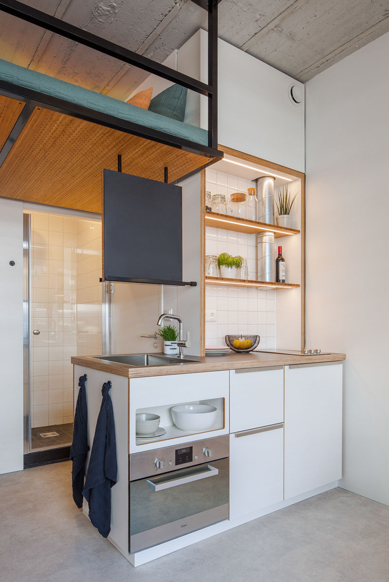 This small apartment has a tiny kitchen with lit up shelving to keep it bright. #SmallKitchen #KitchenDesign #SmallApartment