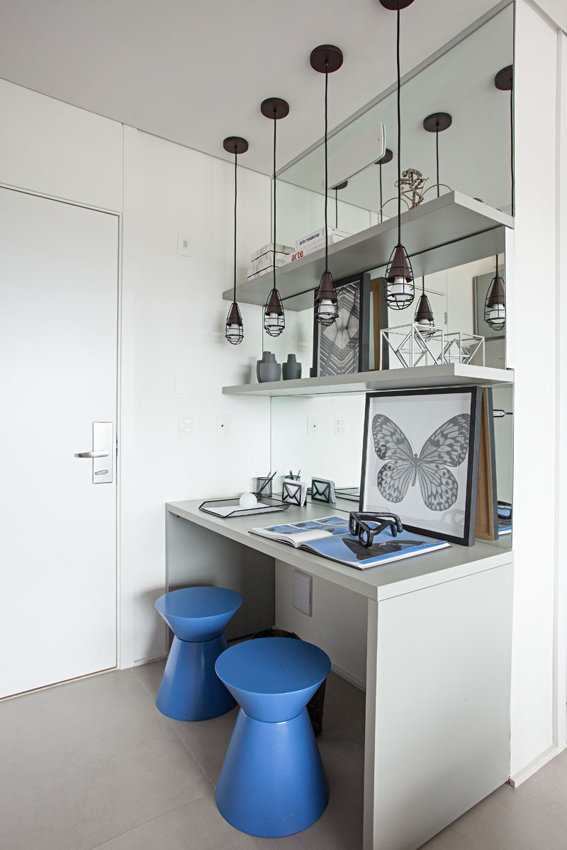 Stepping inside this small apartment, there's a desk area with a mirrored wall, that helps to make the entryway appear larger. #SmallApartment #HomeOffice #MirroredWall