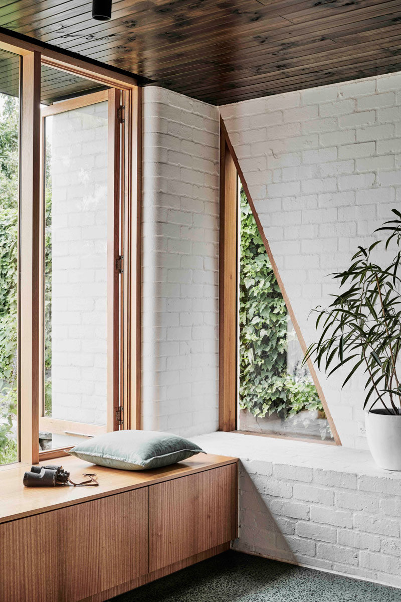 This modern interior features a white brick wall,wood cabinetry and a triangle window in the corner. #InteriorDesign #WhiteBrick #Window #TriangleWindow