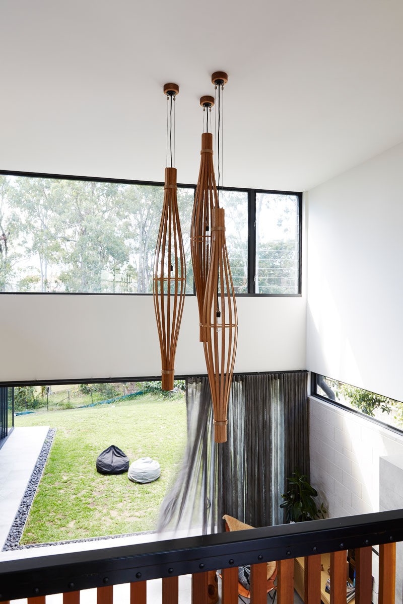 The entryway in this modern house overlooks the living room and backyard, and provides a view of the sculptural pendant lights. #Lighting #InteriorDesign