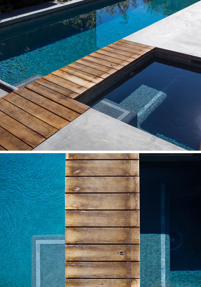 A small wooden walkway makes it easy for someone to walk between the pool and spa. #WoodPath #SwimmingPool #WoodWalkway