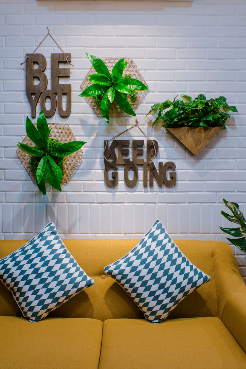 This modern living room features a painted white brick wall, wall plants, a yellow couch, patterned blue cushions and wood wall sayings. Click through to see more photos of this apartment. #LivingRoom #WallDecorIdeas #WallDecor #InteriorDesign