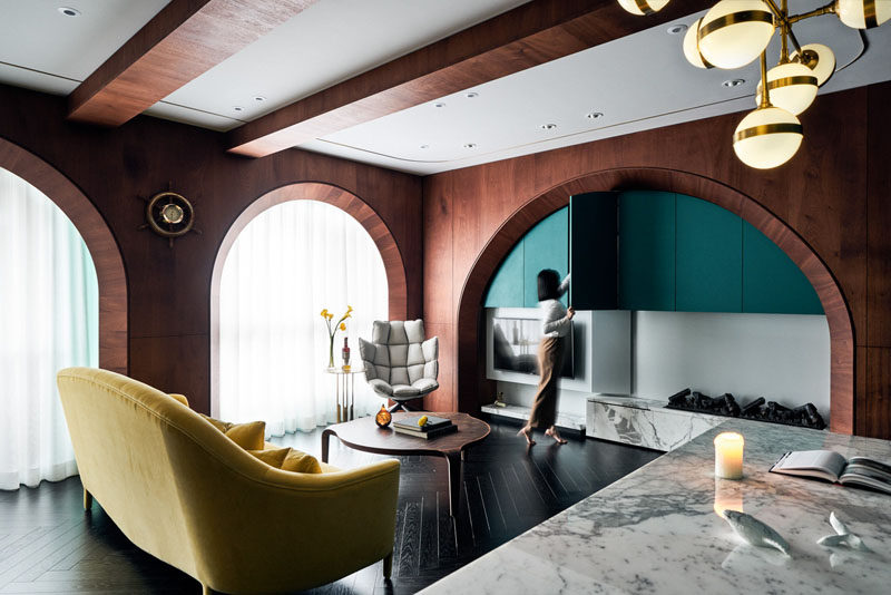 In this modern apartment, a curved arch defines the entertainment center, creates a space for storage and provides a home for the fireplace. The couch can be easily positioned for watching a movie or placed against the windows for a more open floor plan. #Wood #Arches #ModernInterior #ApartmentDesign #InteriorDesign