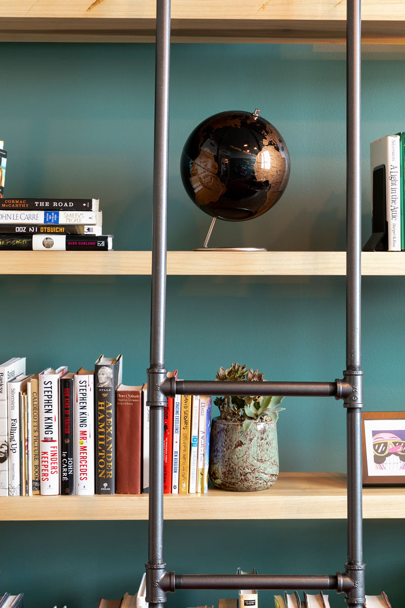 Francis Dominguez has transformed a spare empty bedroom into a library that features wood shelves, a metal ladder, and a reading area. #IndustrialModern #Library #InteriorDesign