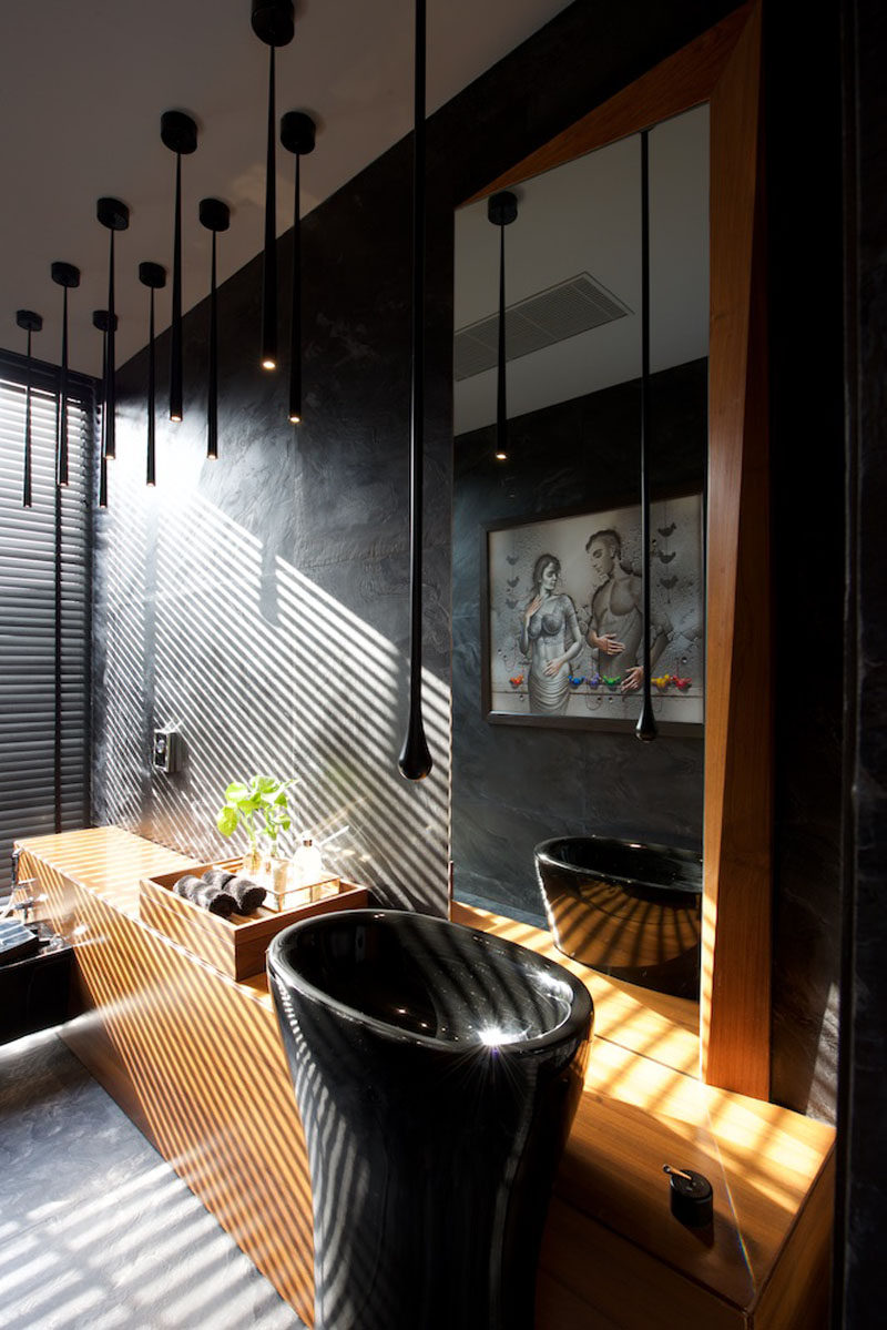 In this bathroom, black slate covers the walls and has been paired with rich wood for a modern and dramatic look. #ModernBathroom #BlackBathroom #BlackAndWoodBathroom