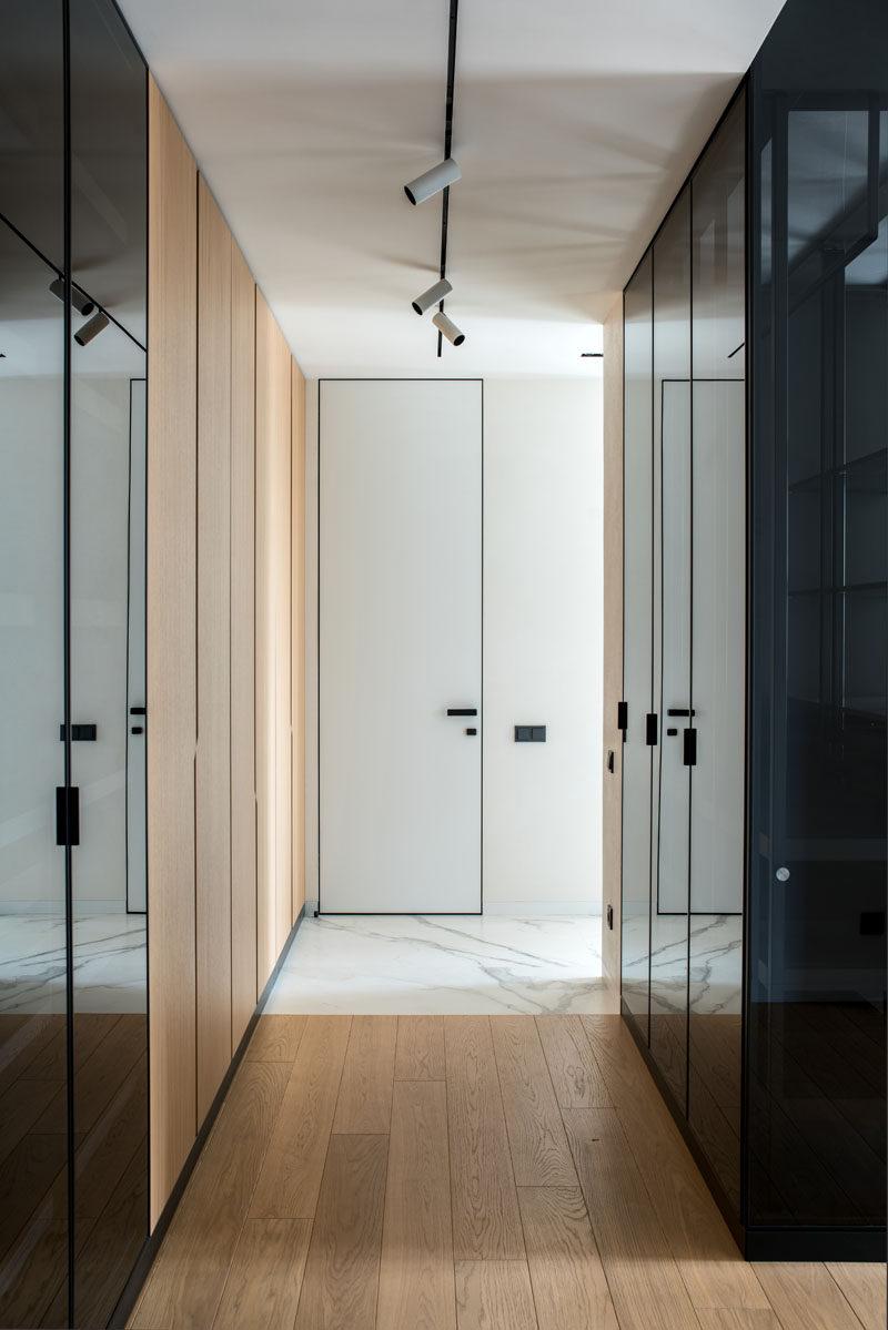 This master bedroom has walls of wood and black glass closets. #Closets #InteriorDesign